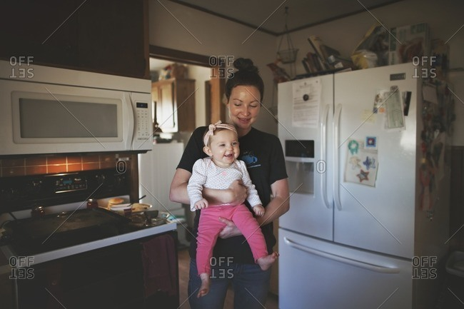 Mom holding grinning girl in kitchen