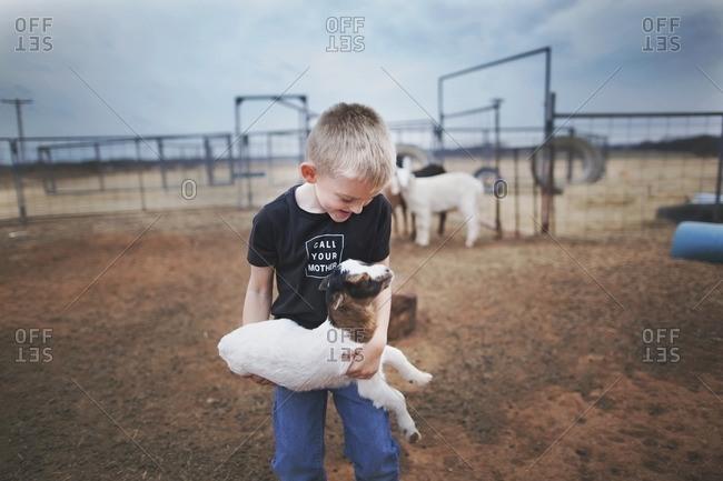 Smiling boy holding baby goat in pen