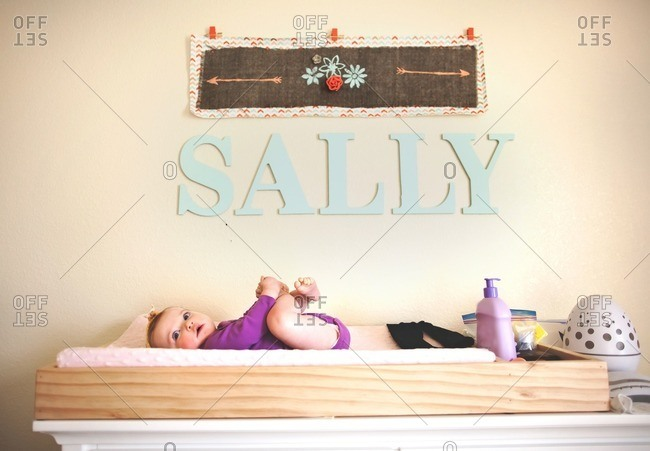 Baby girl lying on changing table