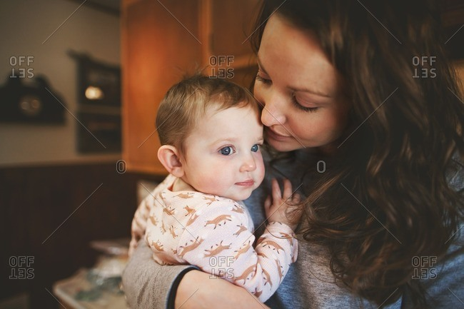 Mom holding baby girl close in home