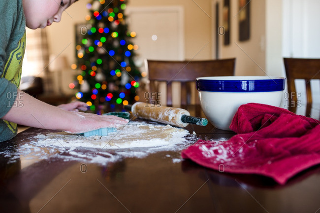 A boy cutting out holiday cookies