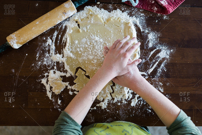 Child cutting out holiday cookies