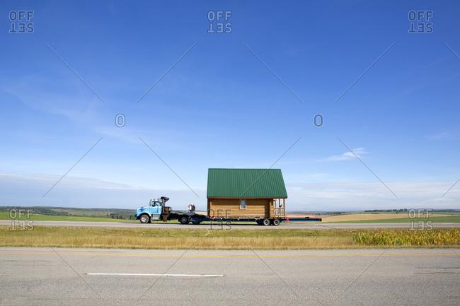 Truck hauling a small cabin