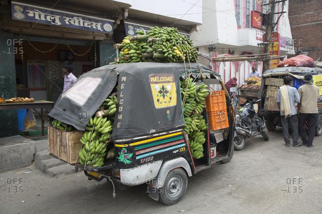 New Delhi, India - February 27, 2015: People by bananas in tuk tuks