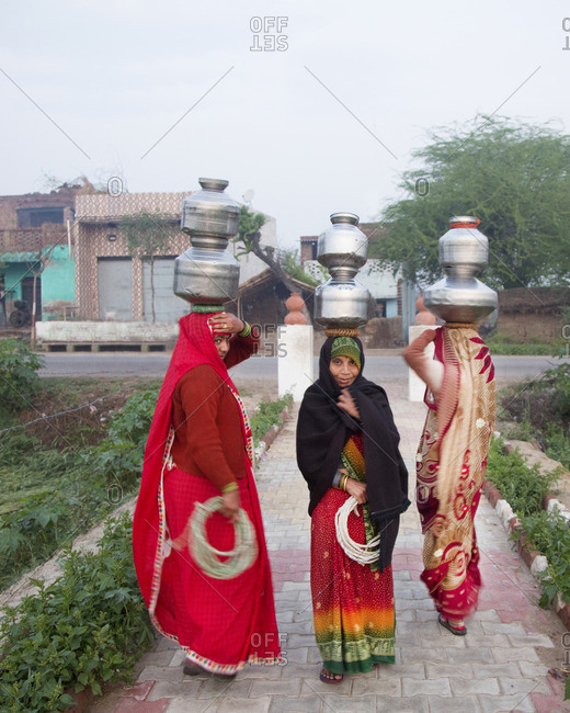Mathura, India - March 5, 2015: Women carrying jugs of water