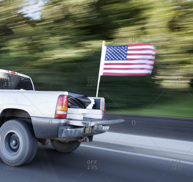 Speeding pickup truck with American flag