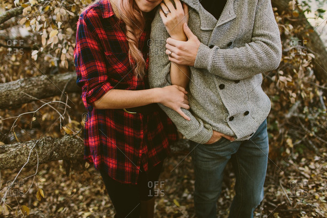 Couple with arms linked in woods