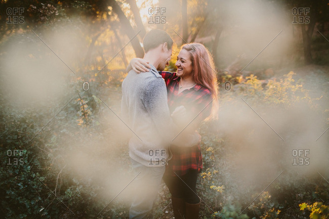 Smiling woman embracing man in woods