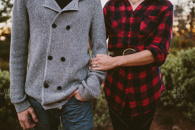 Midsection of couple standing together outdoors