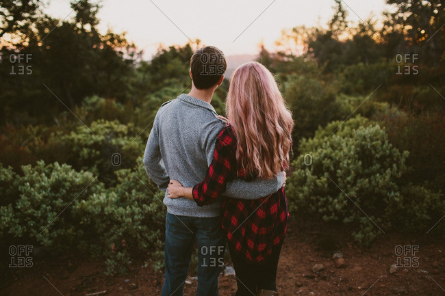 Couple embracing in sunset in autumnal woods