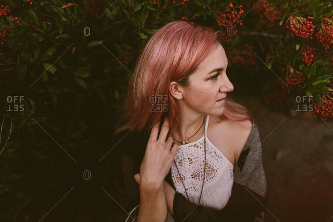 Woman with pink hair by berry bush
