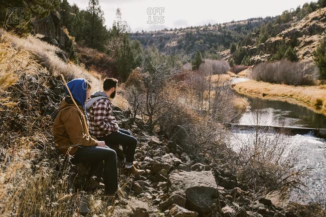 Men over river in autumn mountain setting