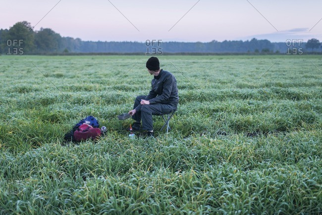 Hiker sitting in field boiling water on camping gas. Noordijkerveld. Achterhoek. Gelderland. The Netherlands.