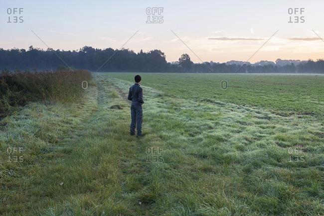 Young man standing in misty meadow on cold morning. Noordijkerveld. Achterhoek. Gelderland. The Netherlands.