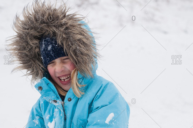Laughing girl wearing a jacket with a furry hood in the snow