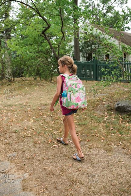 Girl wearing a backpack walking through yard
