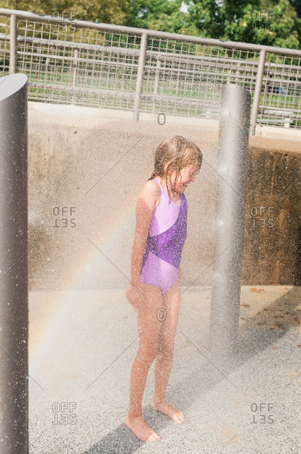 Girl standing in the spray of sprinklers at park