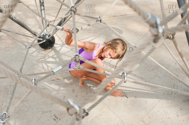 Girl playing at the bottom of playground rope structure