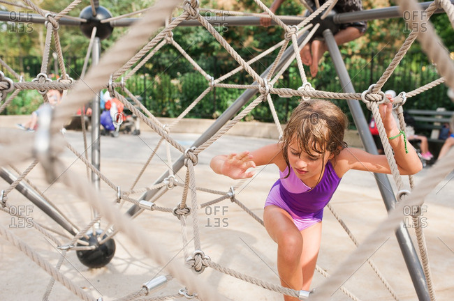 Girl climbing on playground rope structure