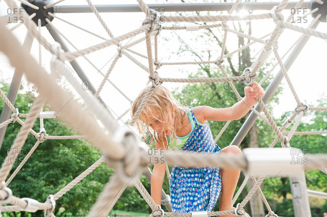 Girl playing near the top of playground rope structure