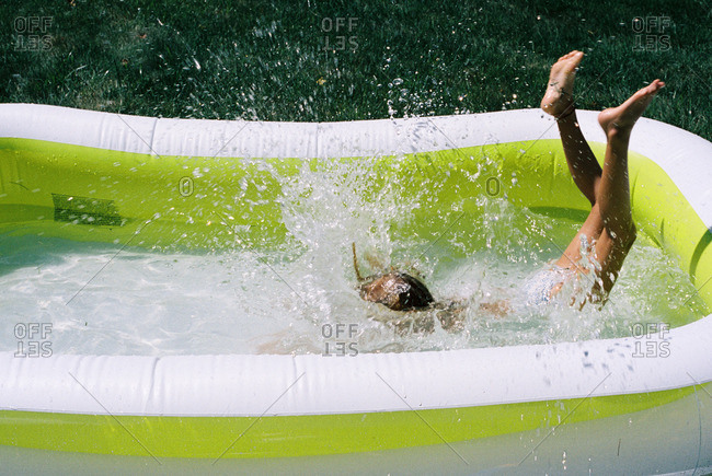 Child jumping into an inflatable pool