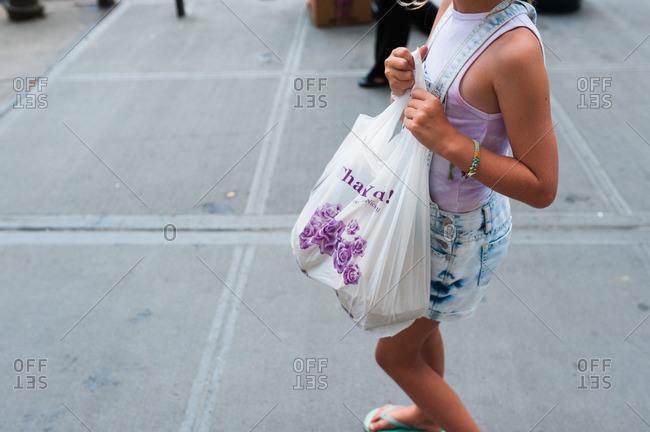Girl carrying a full plastic bag