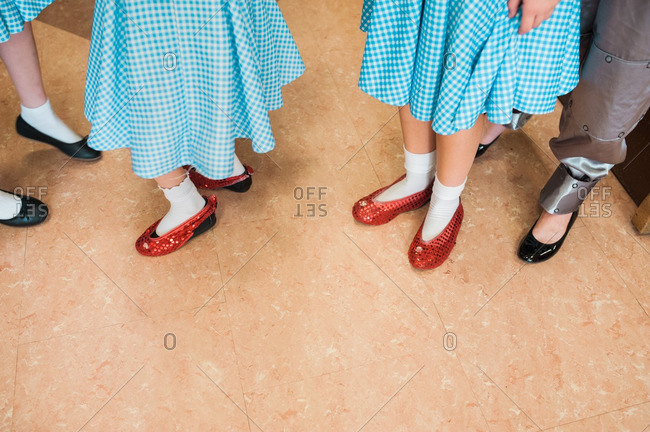 Girls in costume wearing blue gingham dresses and ruby slippers