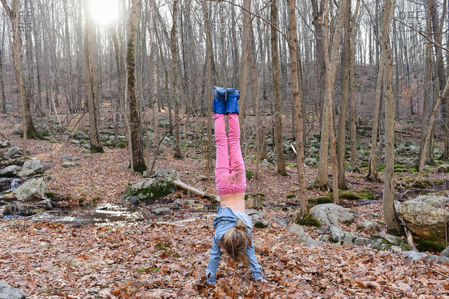 Girl doing handstand in the forest