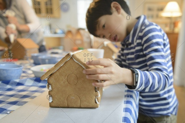 Young boy building a gingerbread house