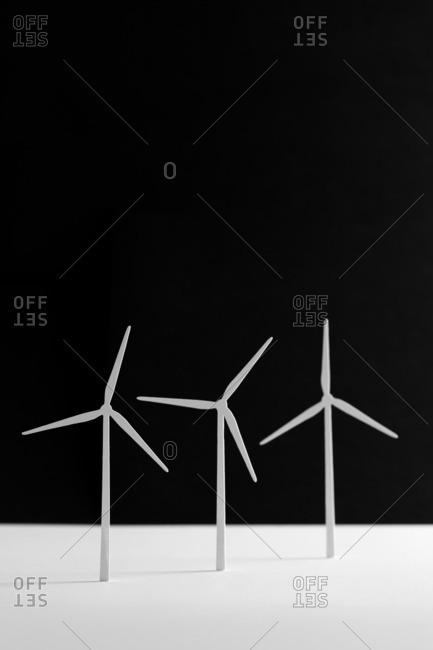 Wind turbine paper cutouts against dark background
