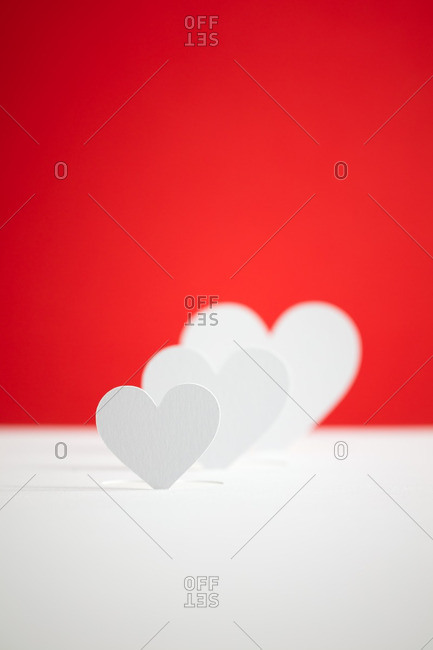 Paper hearts in front of a red background