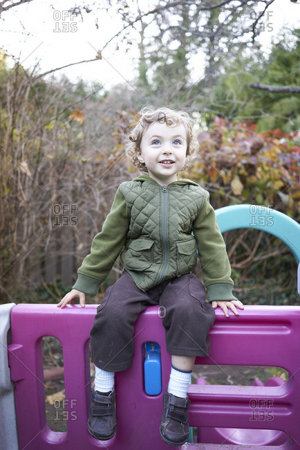Toddler boy playing on a play set in the fall