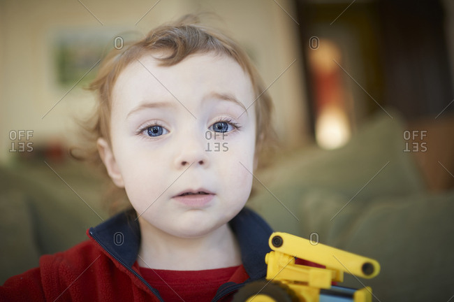 Portrait of a toddler boy with curly hair and blue eyes