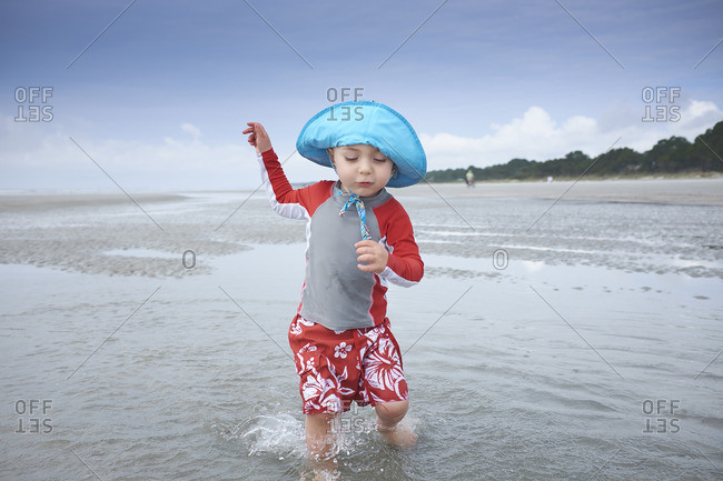 Toddler boy wearing blue hat and red outfit playing in the ocean