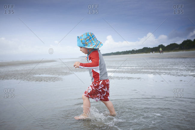 Toddler boy wearing blue hat and red outfit walking in the ocean
