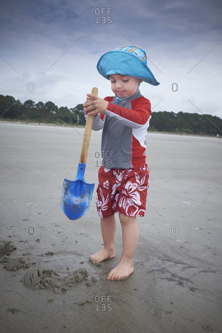 Toddler boy wearing blue hat and red outfit playing on a beach
