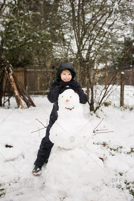 Little boy leaning on a snowman