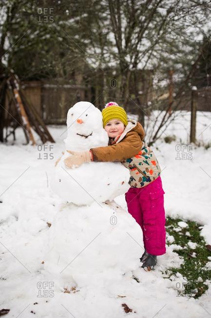 Little girl hugging a snowman