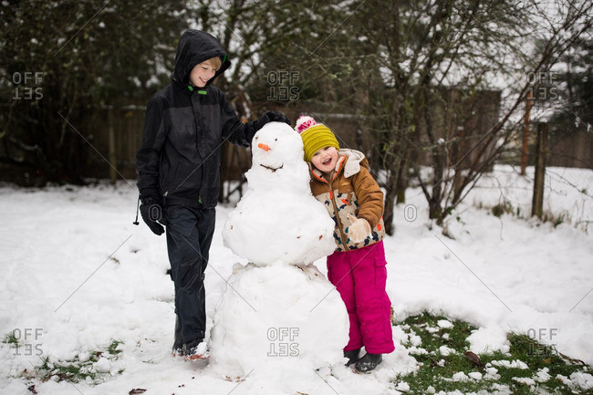Brother and sister standing by a snowman