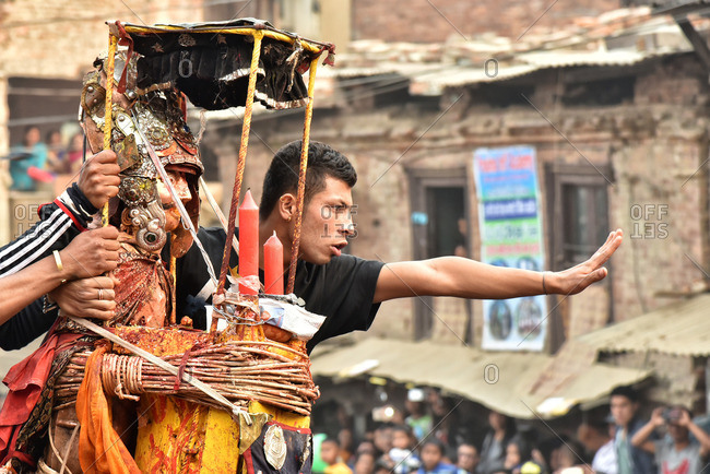 Bakthapur, Nepal - April 13, 2016: People taking a ride in chariot during traditional New Year in Nepal