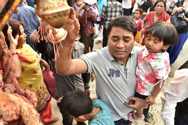 Bakthapur, Nepal - April 13, 2016: Man holding child and touching tinkle on chariot celebrating New Year in Nepal