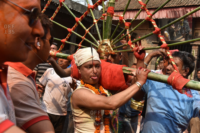 Timi, Nepal - April 14, 2016: Nepalese man carrying heavy traditional chariot with tongue out during New Year celebration