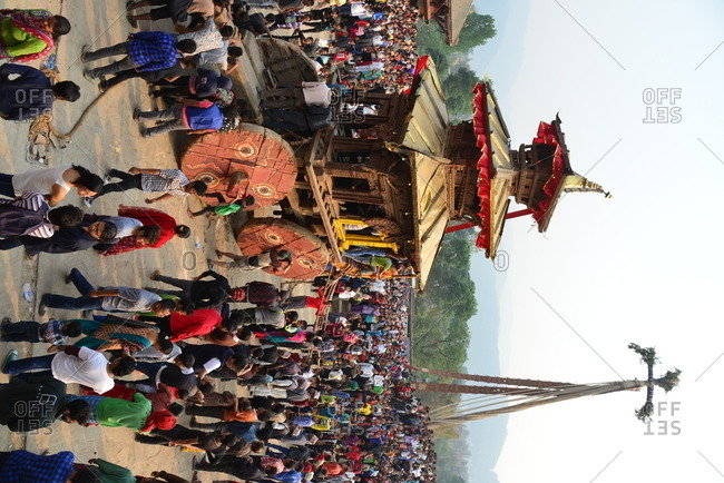 Bakthapur, Nepal - April 13, 2016: a crowd of people following traditional wooden chariot during New Year festival