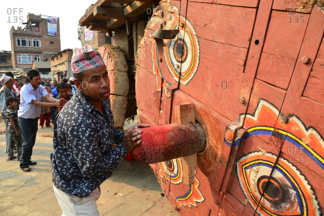 Timi, Nepal - April 13, 2016: Person carrying wooden wheel of big traditional chariot for New Year festival in Nepal