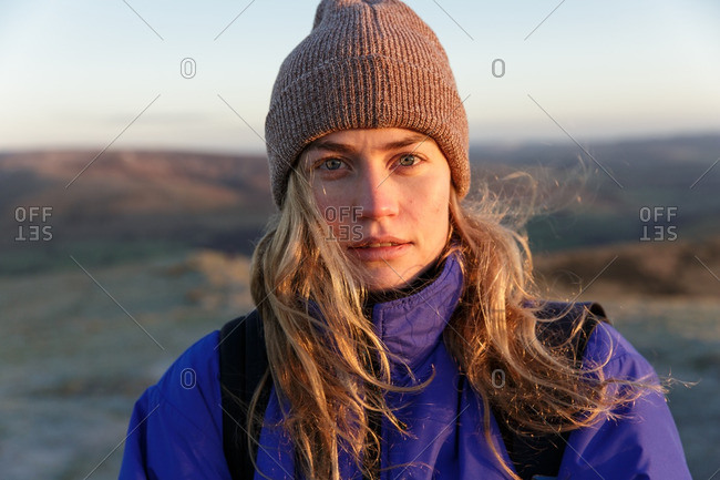 Portrait of a young woman with long hair and knit hat outdoors