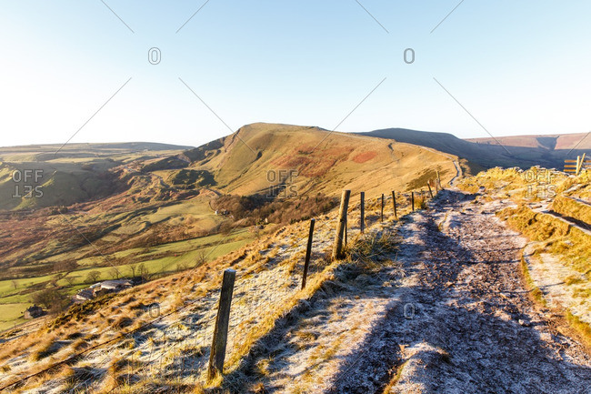 Rural landscape with hills and path covered in frost