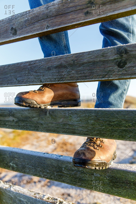 Person wearing boots and jeans climbing on a wooden fence