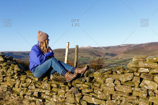 Young woman sitting on stone wall looking into the distance