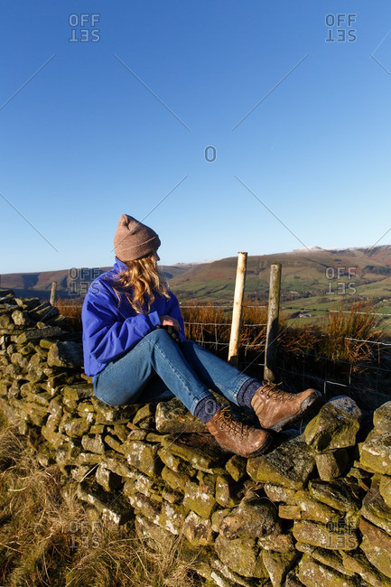 Woman sitting on stone wall looking into the distance