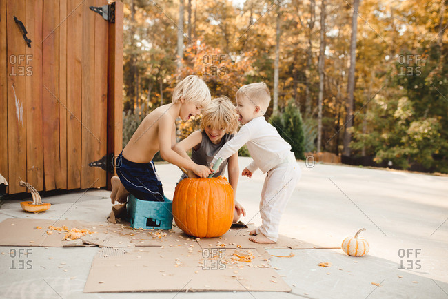 Three boys carving a pumpkin together